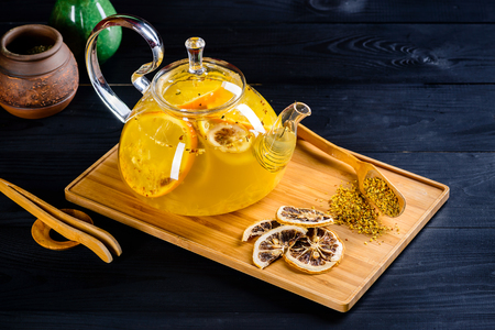 orange ginger tea in a teapot on a wooden table