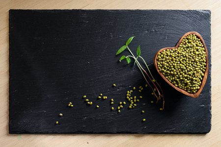microgreen radish grain and germinated sprout on adark background with copy space, heart symbol concept Banco de Imagens