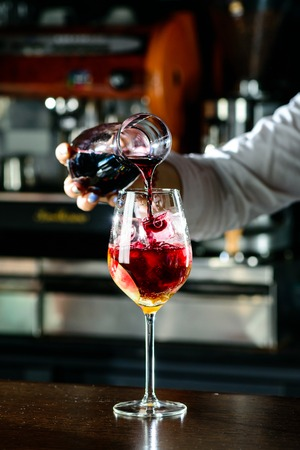 Bartender making Red Sangria in Italian restaurant. Sangria cocktail with red wine on bar blurred background
