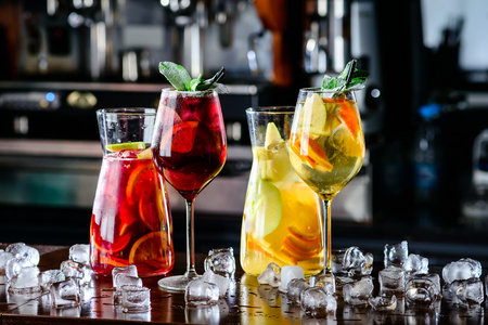White and red sangria with fruit and ice. Summer alcohol drink and ingredients. sangria with red and white wine in decanter with wineglasses in wine glass on bar blurred background Banco de Imagens