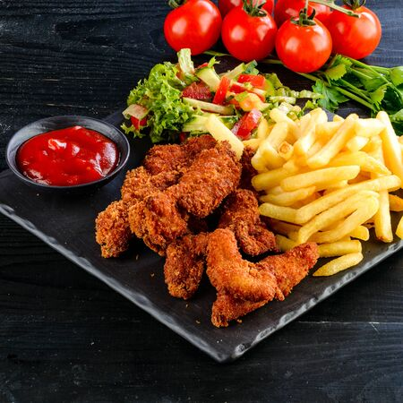 Fried chicken, nuggets and french fries, set of chicken nuggets, salad and french fries on wood table. Food issue.