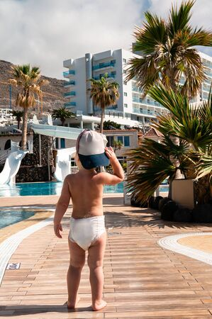 Rear view of a child one baby boy in a diaper at the resort Travelling, vacations