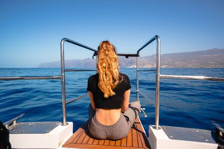 Rear view of a beautiful young blonde girl sits on the bow of the ship and looks at the ocean, cheerful young woman sitting on a luxury yacht Freedom concept. Travelling, vacations Zdjęcie Seryjne