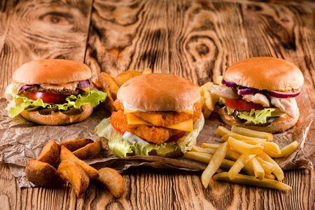 Three burgers on a dark background, in the craft, with potatoes rustic wooden table, delicious chicken, beef and shrimp burgers copy space. Stock fotó
