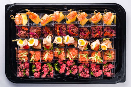 seafood appetizers for a buffet, Canapes of cheese vegetables meat and seafood top view, flat lay
