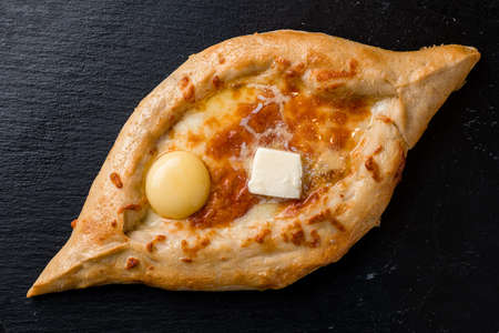 khachapuri with cheese and egg on a plate top view, flat lay