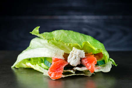 Green burger with lettuce with salmon on a black wooden background
