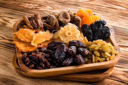 Mix of dried fruits symbols of judaic holiday Tu Bishvat. assorted dried fruits in wooden bowl. organic food background
