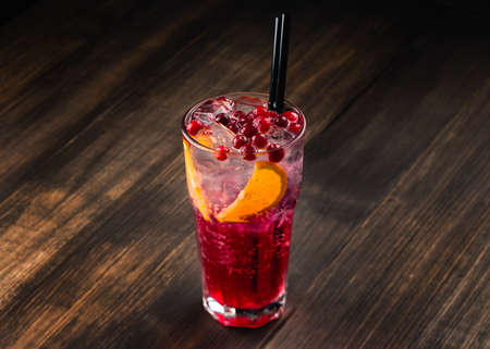 Refreshing cocktail with sparkling water with ice and cranberry, cranberry lemonade with ice, lingonberry cocktail in a tall glass with a straw Archivio Fotografico