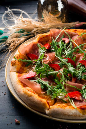 Pizza with prosciutto parma ham, arugula salad rocket and strawberries on wooden background Italian cuisine.