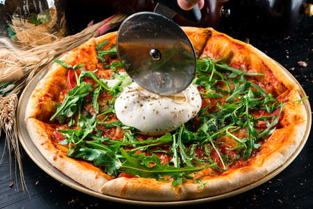 Italian pizza with mozzarella and fresh arugula. Pizza menu. Top view with copy space on dark table