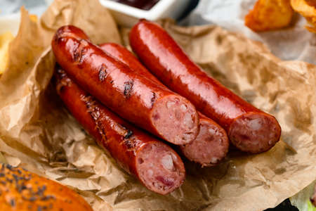 Grilled sausages with tomatoes, red pepper, spices and fresh herbs. Symbolic image. Concept for a tasty and hearty meal. Close up.
