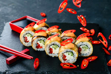Traditional Japanese cuisine. Selective focus on set of sushi rolls with cream cheese, rice, chili pepper on dark background, spicy sushi with eggplant and chili pepper Reklamní fotografie