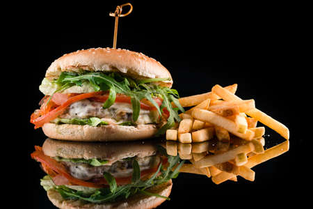 Craft beef burger and french fries on a black background with reflection