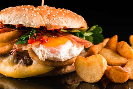 homemade grilled burger with egg and bacon on a black background with reflection close up