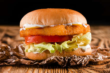 Tasty grilled burger with chicken or fish salmon breaded, fish Burger fishburger or chickenburger on a dark background