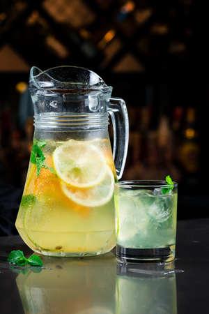Summer fresh cold drink beverages. Ice Lemonade in jug lemons and orange with mint on table. Orange lemonade in a jug