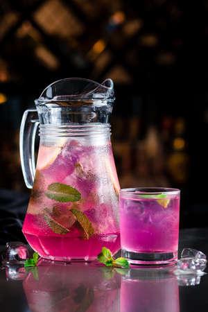 Summer fresh cold drink beverages. Ice Lemonade in jug with mint on table, pink lemonade in a jug Reklamní fotografie