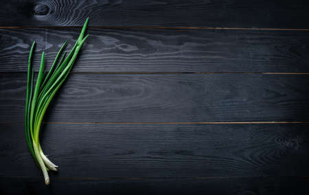 Fresh green onion on a wooden background. Top view. Free space for your text. Copy space