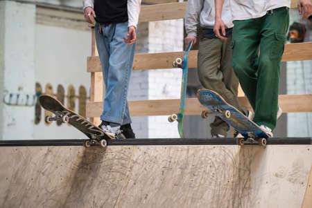Skater standing on ramp in skate park ready to ride skate board and do tricks. Concrete park, focus on skateboard, feet and shoes. Skateboarder boy riding on ramp. Skateboarder ready to roll