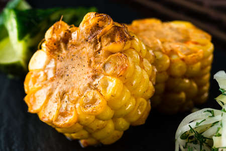 Barbecued sweet corn over dark background, corn grill close up