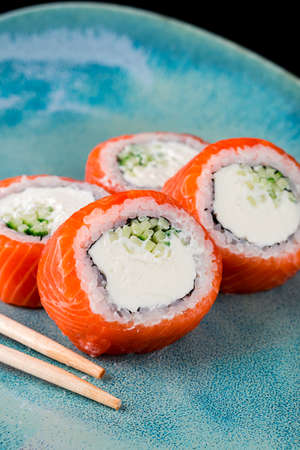 Delicious fresh sushi rolls with salmon and philadelphia cheese. Traditional japanese seafood, healthy food concept sushi roll salmon with cream cheese close-up, vertical food photo