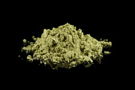 powdered hill green tea isolated, green matcha tea powder on black background