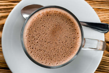 hot chocolate with frothy foam, texture of cocoa hot chocolate in a mug top view closeup