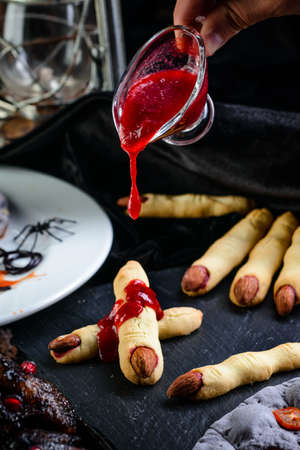 bloody sweet jam pouring on cookies fingers for Halloween party celebration, Cookies Witch's fingers. Dark background, food for Halloween