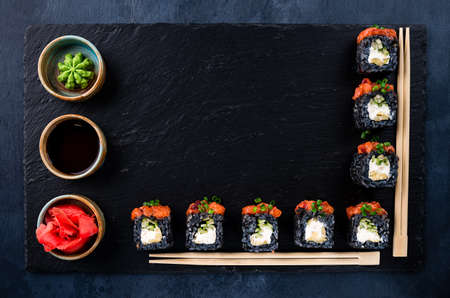 Set of traditional japanese food on a dark background. sushi rolls and chopsticks for sushi Top view. Asian food frame. Dinner party.