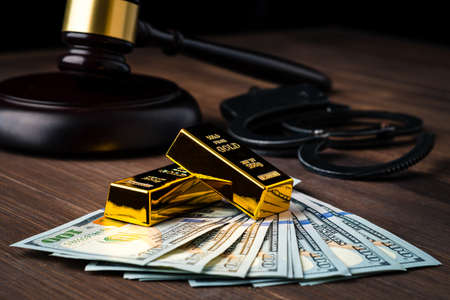 Judge's gavel with dollars and gold, judge's hammer and gold, concept of financial regulation in the price of gold