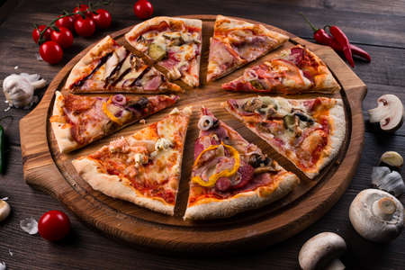 different pizza slices on a round wooden Board, slices of pizza with different toppings on a wooden background