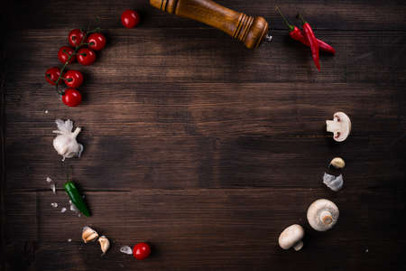 food background circle of tomatoes, mushrooms, pepper and spices on a wooden brown background. cherry tomatoes, garlic arranged in a circle on wooden background.