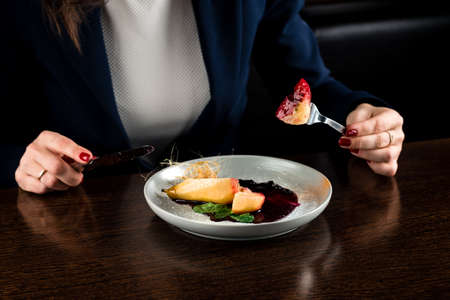 Female hands cuts caramel pears over dark table, woman eats dessert caramelized pear with chocolate 免版税图像