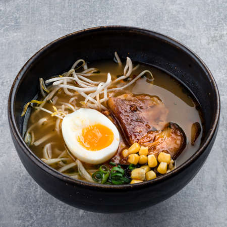 Traditional Japanese soup ramen with meat broth, asian Udon noodles, seaweed, eggs and ginger on dark concrete background. Asian style food. Hot tasty ramen soup for dinner