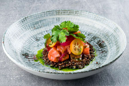 Delicate fillet of salmon on a cushion of quinoa with vegetables, avocado. Restaurant menu raw salmon with quinoa