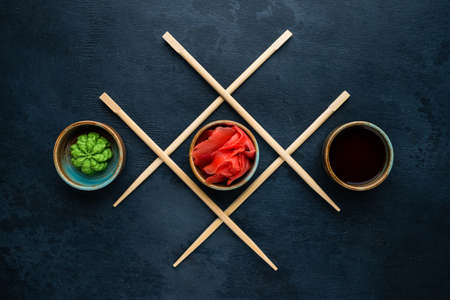 traditional Japanese condiments, composition of wasabi, ginger and soy sauce for sushi top view, flat lay