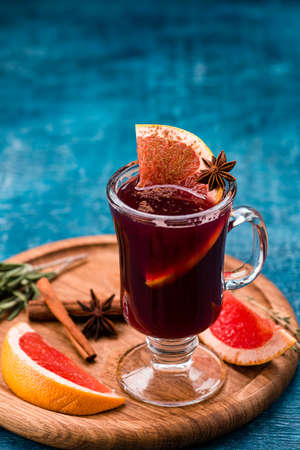 Grapefruit Mulled Wine Punch with cinnamon and grapefruit on wood table with copy space background