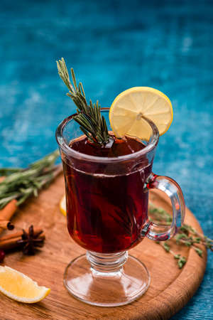 glass cup of hot winter drink with apple, lemon, ginger and spices, mulled wine with lemon with copy space background