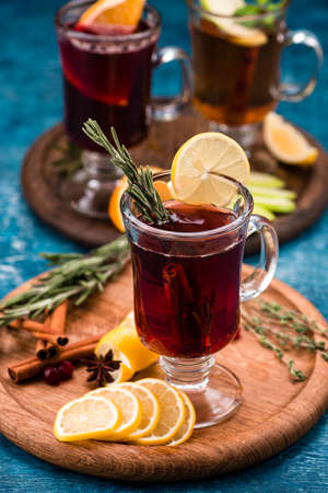 glass cup of hot winter drink with apple, lemon, ginger and spices, mulled wine with lemon 免版税图像