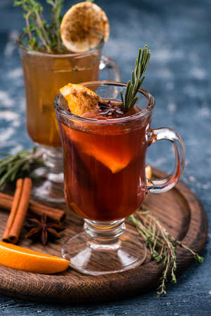 Winter drink with oranges and cloves, traditional mulled wine on a wooden tray