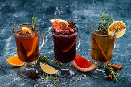 Various autumn or winter seasonal alcohol hot cocktails - mulled wine, grog, warm ginger ale, hot rum, punch, mulled apple cider on gray background copy space 免版税图像