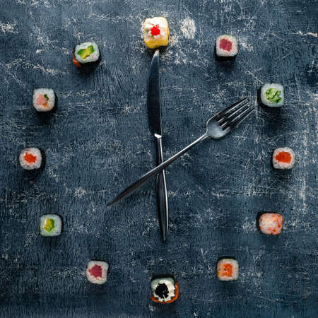 Sushi time in the form of a wall clock on a concrete background, sushi clock with fork and knife, concept of time to eat 免版税图像