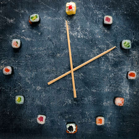 Clock Concept with sushi top view, watch sushi with chopsticks by the arrows, the concept of time to eat 免版税图像