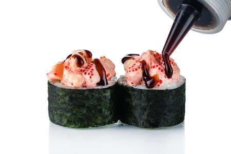 Sushi rolls sauce is poured on top, Japanese traditional roll preparation in close up. The bottle in the air pouring out tasty mayo on tops 免版税图像