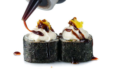 Sushi rolls sauce is poured on top, Japanese traditional roll preparation in close up. The bottle in the air pouring out tasty mayo on tops on white background