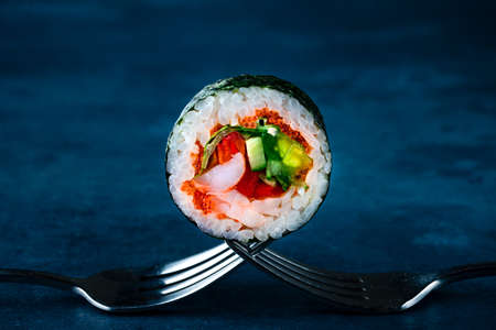 Traditional japanese futomaki roll stuffed with tobiko caviar, cucumber, crab meat and tomato, futomaki Shimoda Maki close up on a fork 免版税图像