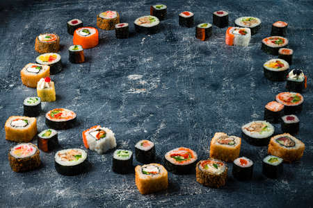 Set of traditional japanese food on a dark background. different sushi rolls in a circle with copy space in the center. Asian food frame. Dinner party. Top view. Copyspace, flat lay