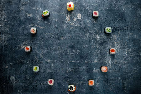 Set of traditional japanese food on a dark background. different sushi rolls in a circle with copy space in the center. Asian food frame. concept twelve hours, twelve months