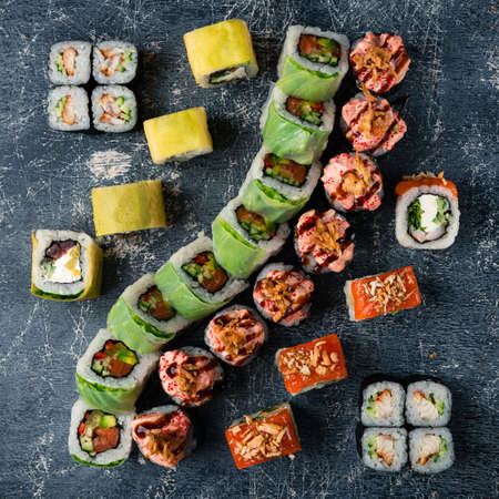 Overhead shot of Japanese sushi on black concrete background, sushi set composition top view